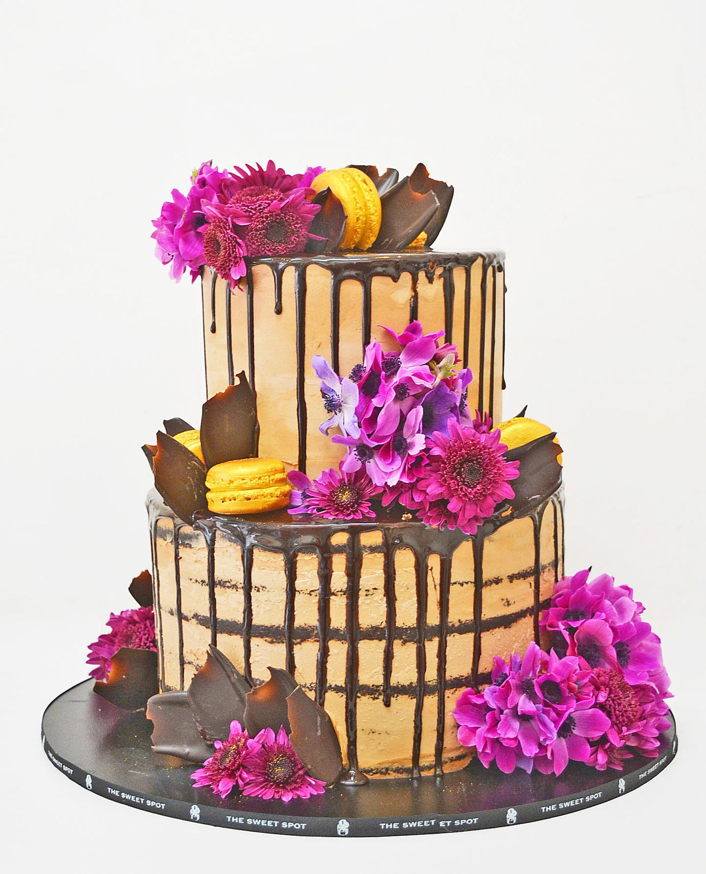 Photo 1 TIERED CHOCOLATE NAKED-DRIP CAKE WITH PURPLE FLOWERS AND MACARONS